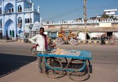 Aziatische handelaar met zijn straatkarretje stock afbeelding