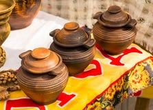 Aziatische het drinken potten Drie schepen met een dekseltribune op een rij, een rustieke achtergrond royalty-vrije stock afbeeldingen