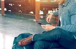 Aziatische hipster slimme mens die mobiele telefoon houden die app lied gebruiken met Stock Foto's