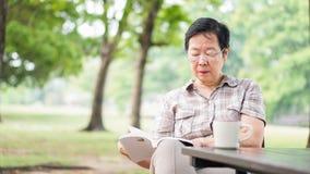 Aziatische hogere het boek van de vrouwenlezing het drinken koffie in zonnig park, g Stock Foto's