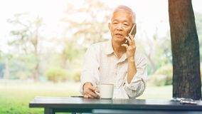 Aziatische hogere mens die op telefoon witte het drinken koffie in park spreken Stock Foto's