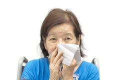 Aziatische hogere vrouw die haar neus blazen Stock Foto's