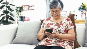 Aziatische hogere vrouw die smartphone met behulp van thuis, gelukkige grootmoeder met in hand technologie de langzame motie 4 k, stock videobeelden