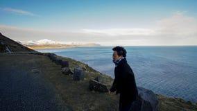 Aziatische hogere vrouwenreis bovenop van de de wegberg van IJsland baai vi Stock Afbeeldingen