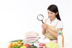 Aziatische huisvrouw met een vergrootglas stock foto's