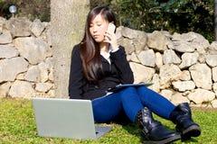 Aziatische jonge bedrijfsvrouw die met technologie in park werken royalty-vrije stock afbeelding