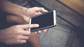 Aziatische jonge jongen die zwarte lege het scherm slimme telefoon op straat houden stock afbeelding