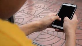 Aziatische jonge jongen die zwarte lege het scherm slimme telefoon op straat houden stock foto's