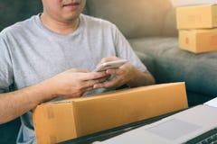 Aziatische jonge mens die smartphone voor thuis het controleren van verzending met behulp van stock foto's