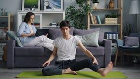 Aziatische jonge mens het praktizeren yoga thuis terwijl zijn vrouw die laptop op bank met behulp van stock footage