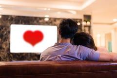 Aziatische jonge minnaars die op televisie op bank letten De paren en ontspannen concept Vakantie en Vakantieconcept Nacht die da royalty-vrije stock afbeelding