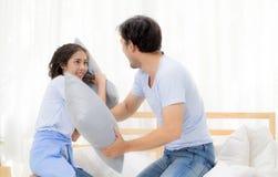 Aziatische jonge paar gelukkige pret met het spelen van hoofdkussenstrijd bij slaapkamer Royalty-vrije Stock Afbeeldingen