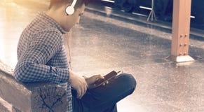 Aziatische jonge slimme mens die mobiele telefoon houden die app lied met l gebruiken Royalty-vrije Stock Afbeeldingen