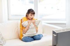 Aziatische jonge vrouw die op TV thuis letten Royalty-vrije Stock Fotografie