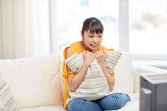 Aziatische jonge vrouw die op TV thuis letten Stock Fotografie