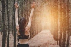 Aziatische jonge vrouw die yoga doen en wapens in bos Achtermening uitspreiden Aard en Gezond Sportconcept Inhaleer verse lucht i stock afbeeldingen