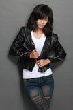Aziatische jonge vrouw in zwart leerjasje op grijze achtergrond stock foto