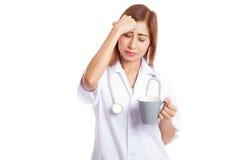Aziatische jonge vrouwelijke arts geworden hoofdpijn met een kop van koffie Royalty-vrije Stock Afbeelding