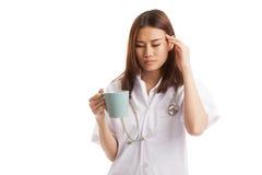 Aziatische jonge vrouwelijke arts geworden hoofdpijn met een kop van koffie Stock Afbeeldingen