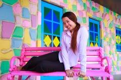 Aziatische jonge vrouwen die op roze stoel zitten Royalty-vrije Stock Afbeeldingen