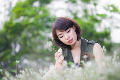 Aziatische jonge vrouwen die op weide zitten Stock Foto's