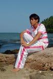 Aziatische jongen in danskostuum dromerig op het strand. royalty-vrije stock afbeeldingen