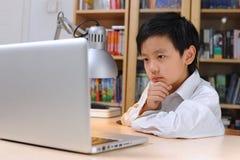 Aziatische jongen die aan computer werken Stock Foto's