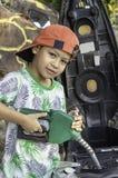 Aziatische jongen die brandstof opvullen in de motor stock afbeeldingen