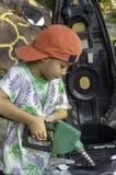 Aziatische jongen die brandstof opvullen in de motor stock foto