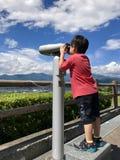 Aziatische jongen die door telescoop met blauwe hemelachtergrond kijken stock foto's