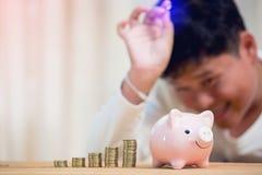 Aziatische jongen die een muntstuk opnemen in een spaarvarken stock foto's