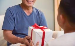 Aziatische Jongen die een witte giftdoos geven aan zijn grootvader Royalty-vrije Stock Afbeeldingen