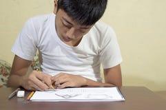 Aziatische jongen die en om 3D vormen leren op tekeningsnotitieboekje op bruin bureau praktizeren thuis te trekken Royalty-vrije Stock Foto's