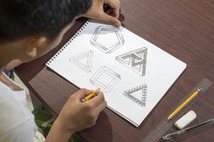 Aziatische jongen die en om 3D vormen leren op tekeningsnotitieboekje op bruin bureau praktizeren thuis te trekken Royalty-vrije Stock Foto