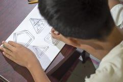 Aziatische jongen die en om 3D vormen leren op tekeningsnotitieboekje op bruin bureau praktizeren thuis te trekken Stock Afbeelding