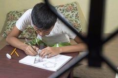 Aziatische jongen die en om 3D vormen leren op tekeningsnotitieboekje op bruin bureau praktizeren thuis te trekken Royalty-vrije Stock Fotografie