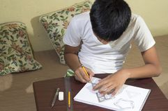 Aziatische jongen die en om 3D vormen leren op tekeningsnotitieboekje op bruin bureau praktizeren thuis te trekken Stock Fotografie