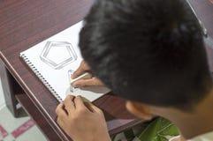 Aziatische jongen die en om 3D vormen leren op tekeningsnotitieboekje op bruin bureau praktizeren thuis te trekken Stock Foto's