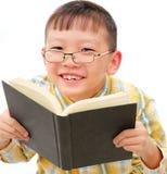 Aziatische jongen die met glazen een boek houdt royalty-vrije stock foto