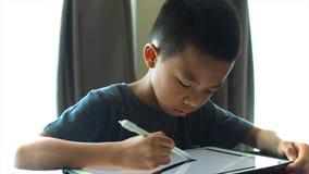 Aziatische jongen die op digitale tablet trekken stock footage