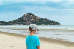 Aziatische jongen die op het strand door het overzees lopen royalty-vrije stock fotografie