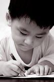 Aziatische jongen die op papier trekt stock foto