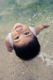 Aziatische jongen die pret op strand heeft royalty-vrije stock foto's
