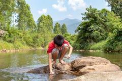 Aziatische jongen die vissen in een stroom bekijken De Aziatische jongens voeden de vissen in de stroom stock foto