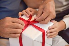 Aziatische jongen en bejaardeholding op rood lint van witte gift BO Stock Foto's
