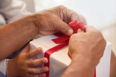 Aziatische jongen en bejaardeholding op rood lint van witte gift BO Royalty-vrije Stock Afbeelding