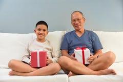 Aziatische Jongen en zijn Grootvaderzitting op witte bank Stock Fotografie
