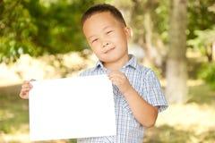 Aziatische jongen 6 jaar oud met een blad van document Stock Afbeelding