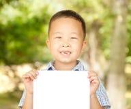 Aziatische jongen 6 jaar oud met een blad van document in het park Stock Foto