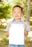 Aziatische jongen 6 jaar oud met een blad van document in het park Royalty-vrije Stock Afbeeldingen
